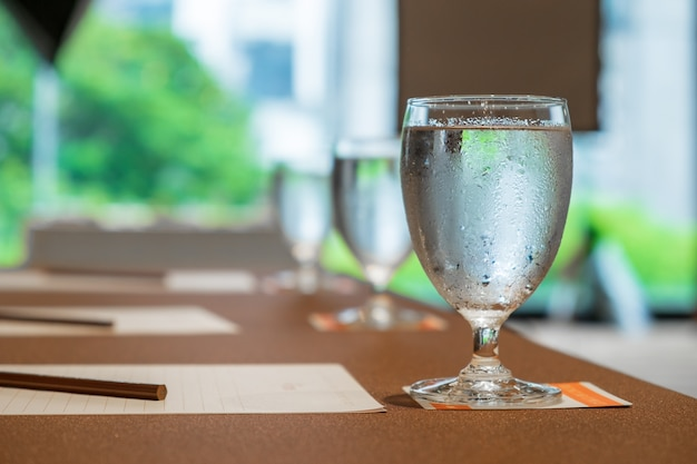 Cold water in a glass with water drop on a table for drink in meeting seminar room