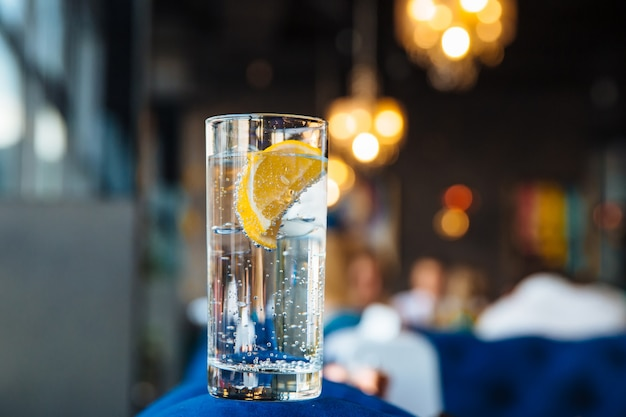 Cold water in a transparent sakan with ice with lemon.