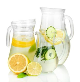 Холодная вода с лимоном, огурцом и льдом в кувшинах, изолированные на белом