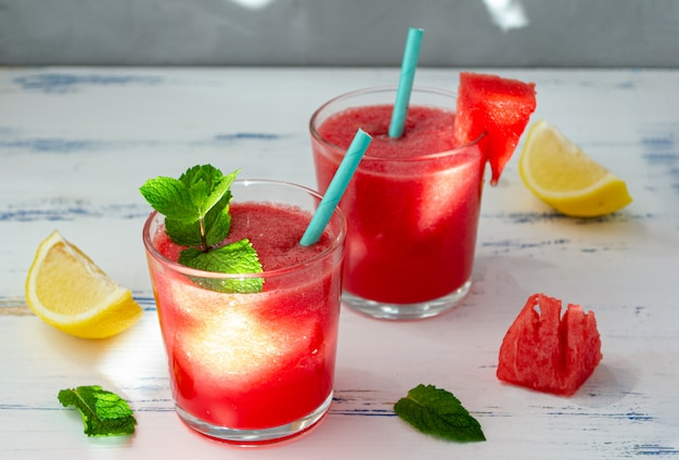Cold watermelon smoothie with mint and lemon in glasses. a cocktail of watermelon juice