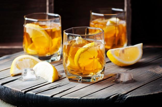 ヴィンテージテーブルの上の氷とレモンの冷たいウイスキー