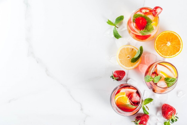 Cold white, pink and red sangria cocktails with fresh fruits, berries and min