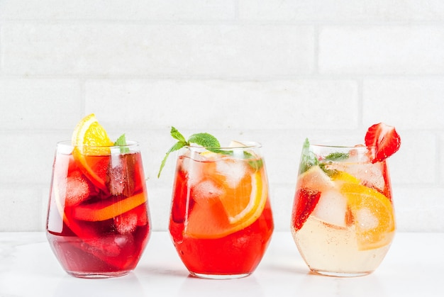 Cold white pink and red sangria cocktails with fresh fruits berries and mint.