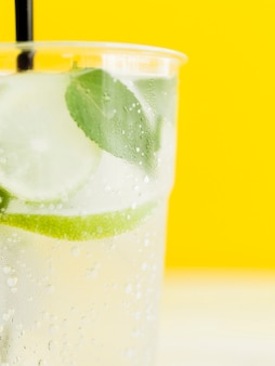 Cold white tasty cocktail with lime, mint and ice on yellow background