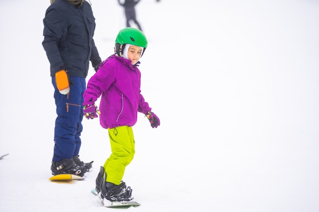 At cold winder day at mountain ski resort father teaching little daughter snowboarding