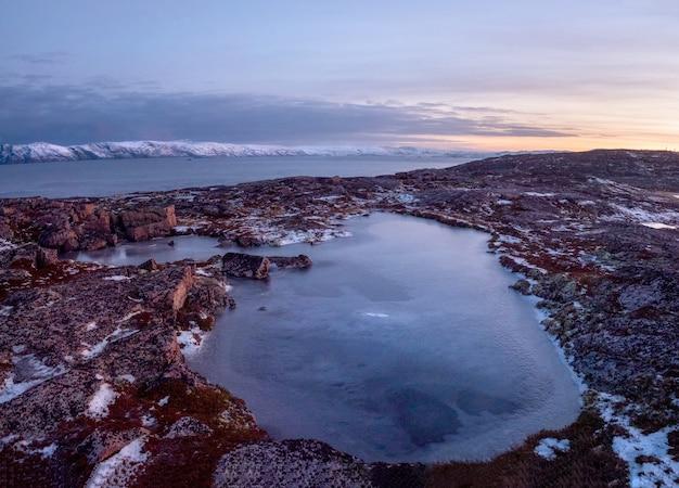 寒い冬の夜明け。ロシアの氷のような風景と山々