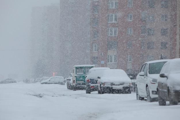 눈, 눈보라, 바람이 몰아치는 추운 겨울 아침. 빈 도시???? 눈으로 덮인 차들과 함께