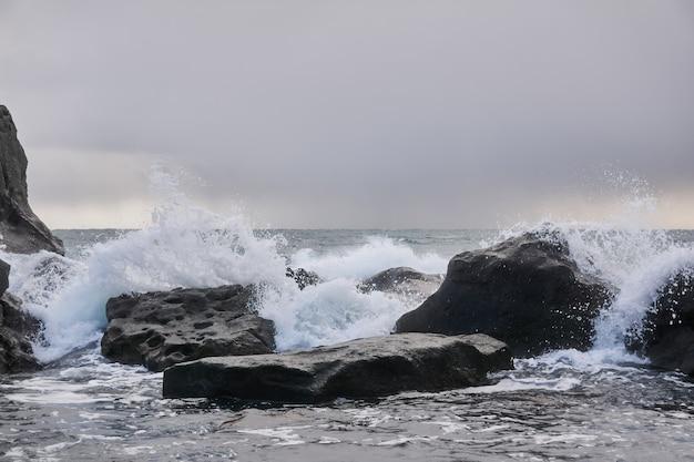 Холодное зимнее море под облачным небом за прибрежными скалами