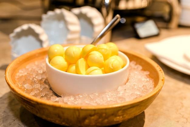 Холодное желтое масло в форме шариков в белой миске, в ледяном ресторане, где подают