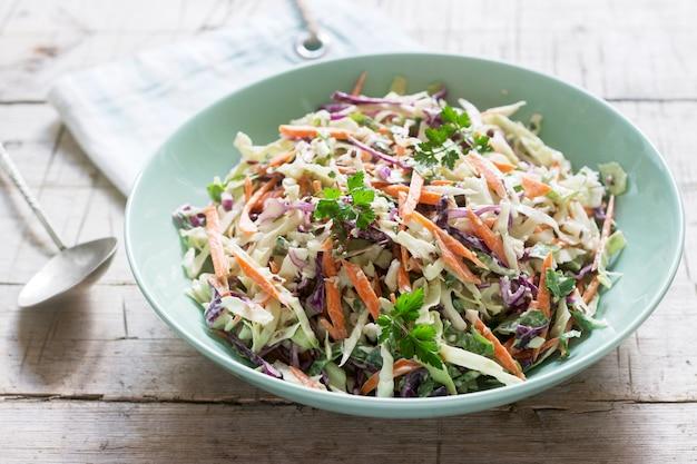 Салат из капусты, моркови и различных трав с майонезом в большой тарелке на деревянном фоне.