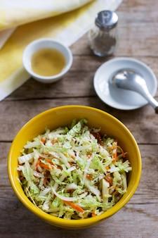 Салат из капусты, моркови и различных трав с майонезом в большой тарелке на деревянной поверхности
