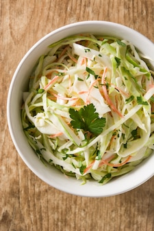 Coleslaw salad in white bowl on wooden table. top view
