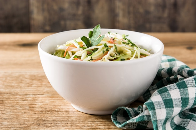 Coleslaw salad in white bowl on wooden table