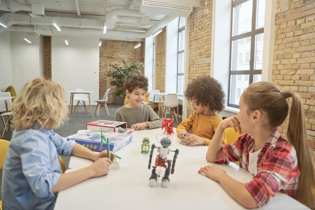 세부 사항으로 가득 찬 기술 장난감을 검사하는 테이블에 앉아 협업 영리한 다양한 아이들 프리미엄 사진