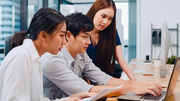 Совместный процесс мультикультурных бизнесменов, использующих презентацию на ноутбуке и коммуникационную встречу для мозгового штурма идей о стратегии успеха рабочего плана коллег в современном офисе.