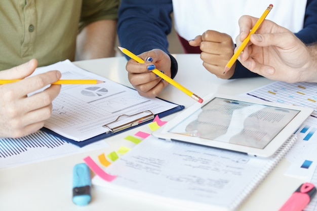 공동 작업. 시작 프로젝트에서 함께 작업하는 마케팅 전문가 그룹, 종이 및 디지털 태블릿 시트와 함께 테이블에 앉아.
