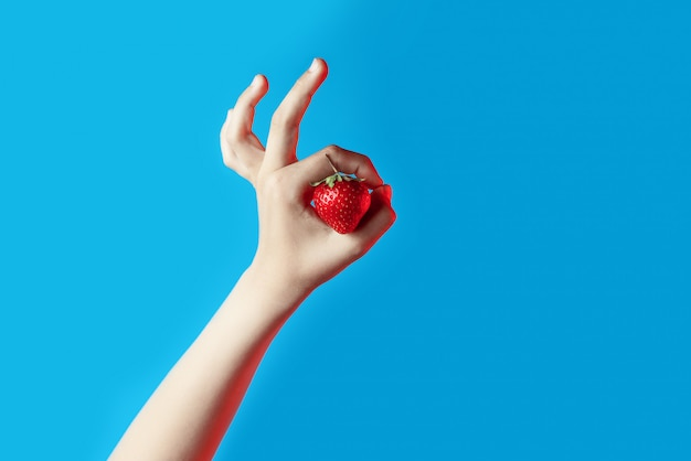 Collage of bright juicy strawberries in hand on blue background