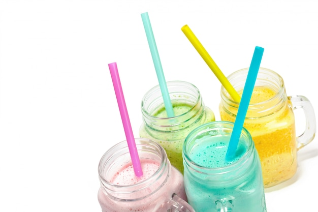 Collage of glass jars with fresh delicious smoothie and straw on white
