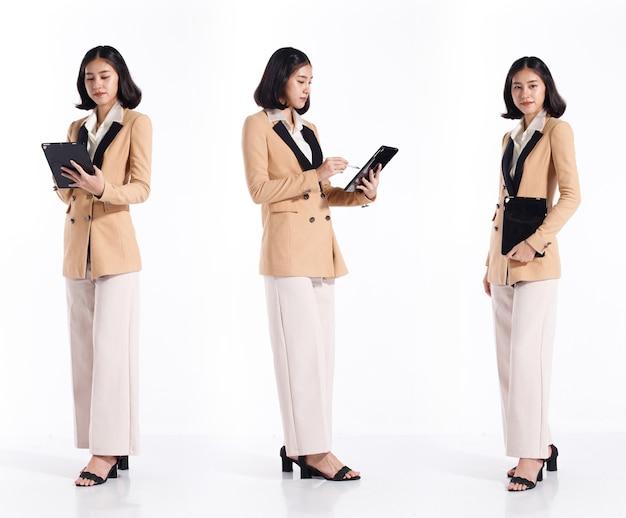 Collage group полная длина оснастка фигуры азиатской женщины 20-х годов черный костюм с короткими волосами в строгом блейзере. бизнес-офис девушка стоит и проверяет цифровой планшет для встречи по электронной почте на белом фоне изолированы