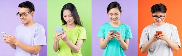 携帯電話を使用し、多色の背景に分離されたアジア人のコラージュ
