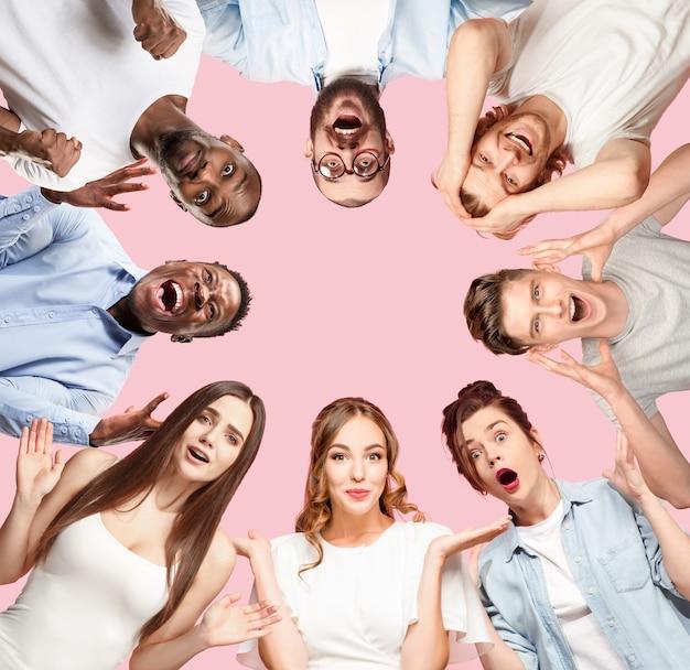 Коллаж из портретов 8 молодых людей на кораллово-розовом фоне крупным планом. человеческие эмоции, концепция выражения лица. празднование, удивление, ощущение победителя, удивление и шок.