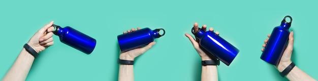Коллаж женской руки, держащей многоразовую эко, алюминиевую термо-бутылку с водой фантомного синего цвета, изолированную на стене цвета морской волны.