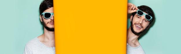 청록색 음영을 입은 젊은 남자의 콜라주 초상화, 복사 공간이있는 주황색과 아쿠아 menthe 색상의 두 배경 사이에 서 있습니다.