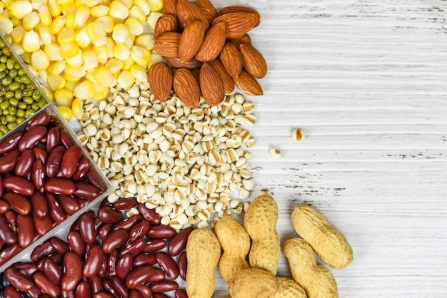 さまざまな豆をコラージュして、食材を調理するための自然な健康食品のエンドウ豆の農業-さまざまな全粒穀物の豆と豆類の種子のレンズ豆とナッツのカラフルなスナック、上面図のセット