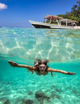 여자 다이빙 수중과 물 표면에 항해 보트와 콜라주