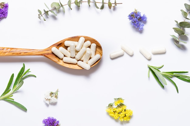Collagen capsules for skincare and beauty in the wooden spoon