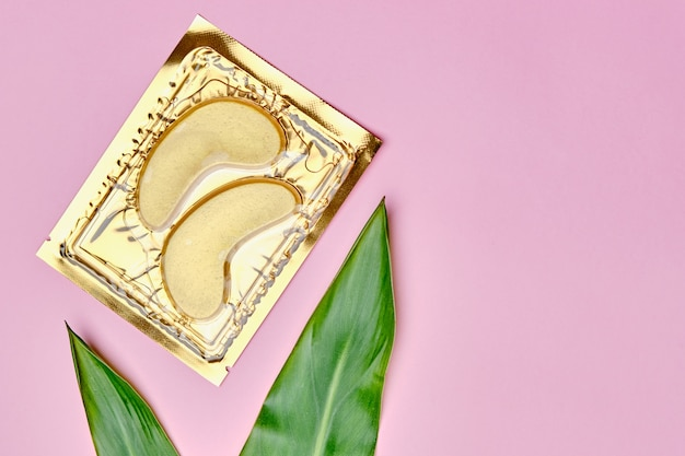 Collagen golden cosmetic eye patches and green leaves. skin care and cosmetology concept.