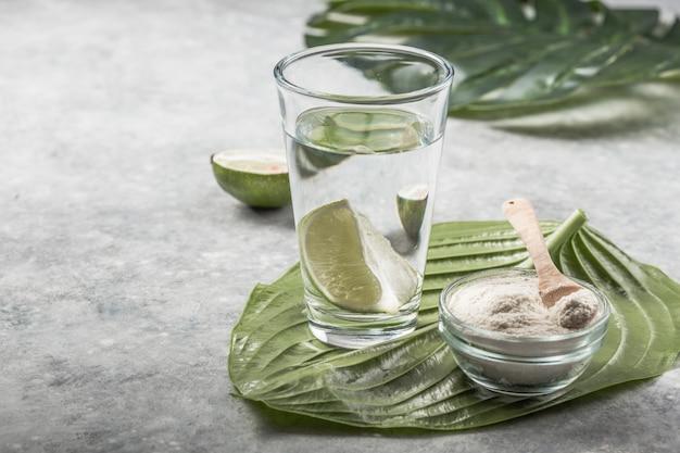 ライムのスライスとコラーゲンパウダーと水のグラス。ビタミンc 。コラーゲンサプリメントは、しわや乾燥を減らすことにより、皮膚の健康を改善するかもしれません。