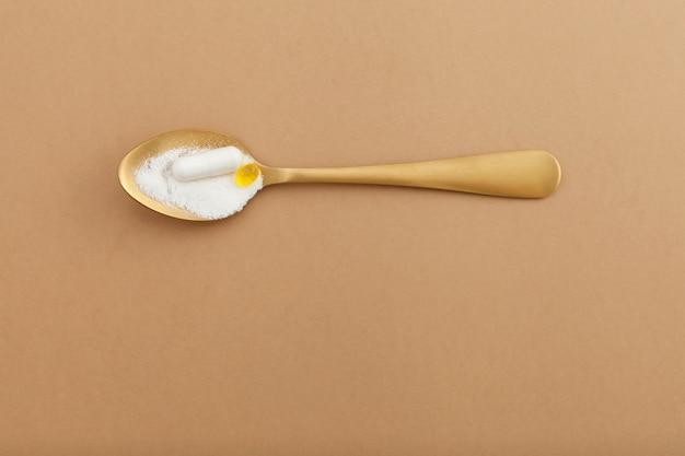 金色のスプーンにコラーゲン粉末と丸薬。