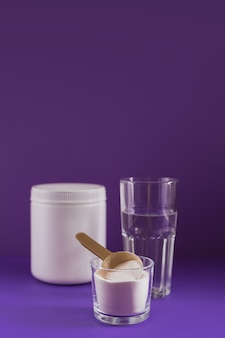 Collagen powder in bowl, glass of water and measure spoon on purple background. extra protein intake. natural beauty and health supplement concept.