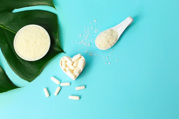 Collagen powder in bowl and pills top on palm leaf on blue background.