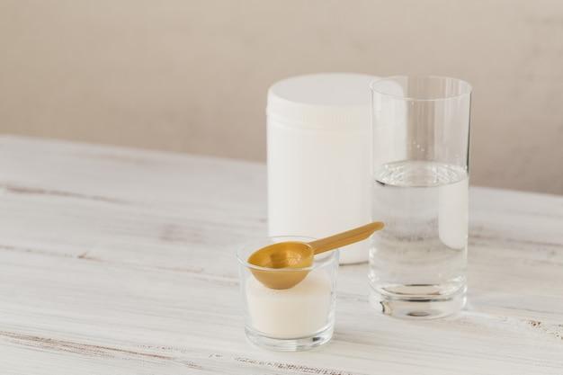 ボウルにコラーゲンパウダー、コップ一杯の水、白い木製の計量スプーン。