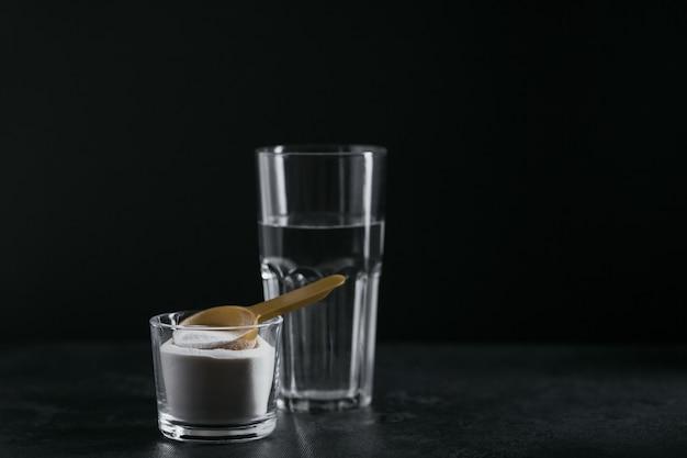 ボウルにコラーゲン粉末、水のガラス、黒の背景に計量スプーン。余分なタンパク質摂取。自然の美しさと健康のサプリメントの概念。