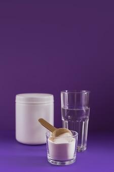 ボウルにコラーゲン粉末、水のガラスと紫色の背景に計量スプーン。余分なタンパク質摂取。自然の美しさと健康のサプリメントの概念。