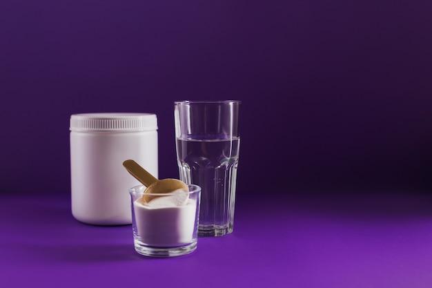 ボウルにコラーゲンパウダー、コップ一杯の水、紫の計量スプーン。