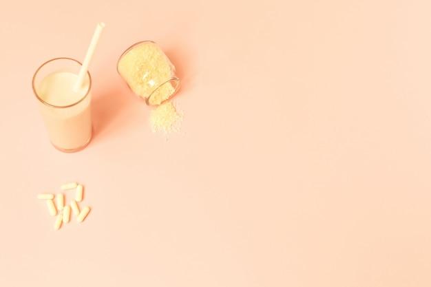 Collagen powder, milk and pills on pink background.