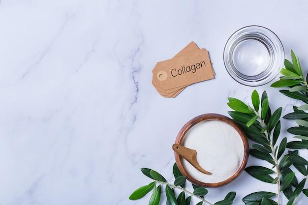 녹색 올리브 나무 잎이 있는 세련된 대리석 배경에 콜라겐 가루. 자연의 아름다움과 건강 보조 식품, 웰빙 스킨케어 노화 방지 개념. 평면도, 평면도, 복사 공간