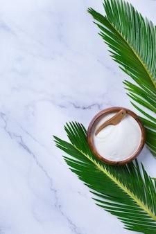 녹색 야자수 잎이 있는 세련된 대리석 배경에 콜라겐 가루. 자연의 아름다움과 건강 보조 식품, 웰빙 스킨케어 노화 방지 개념. 평면도, 평면도, 복사 공간