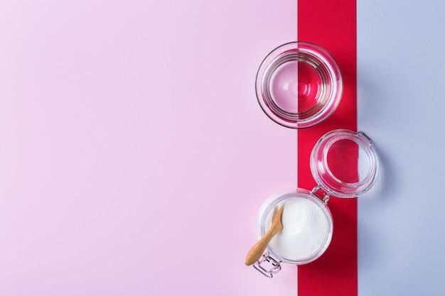 トレンディなピンクの背景にコラーゲンパウダー。自然の美しさと健康のサプリメント、ウェルネススキンケアアンチエイジングのコンセプト。上面図、フラットレイ、コピースペース
