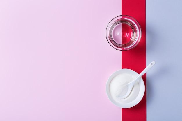 트렌디한 분홍색 배경에 콜라겐 가루. 자연의 아름다움과 건강 보조 식품, 웰빙 스킨케어 노화 방지 개념. 평면도, 평면도, 복사 공간