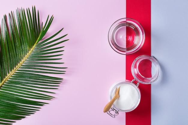 녹색 야자수 잎이 있는 트렌디한 분홍색 배경에 콜라겐 가루. 자연의 아름다움과 건강 보조 식품, 웰빙 스킨케어 노화 방지 개념. 평면도, 평면도, 복사 공간