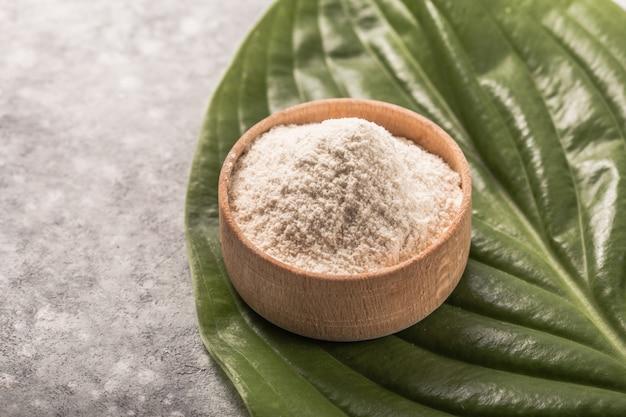コピースペースを持つ緑の織り目加工の葉の背景上のコラーゲンパウダー。栄養補助食品
