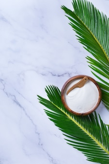 Collagen powder on a trendy marble background with green palm leaves. natural beauty and health supplement, wellness skincare anti-aging concept. top view, flat lay, copy space