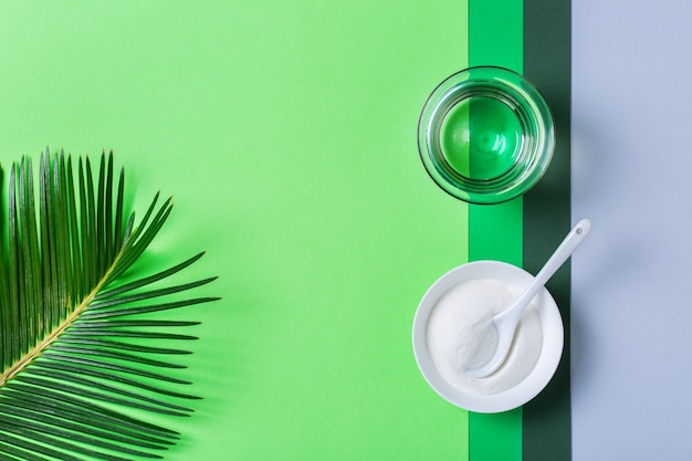 Collagen powder on a trendy mint background with green palm leaves. natural beauty and health supplement, wellness skincare anti-aging concept. top view, flat lay, copy space