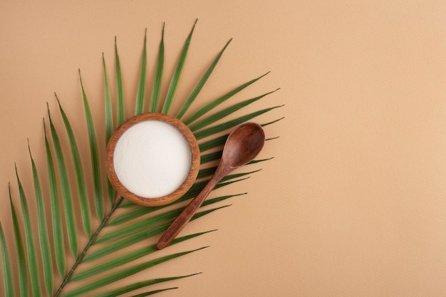 Collagen powder in a wooden bowl, spoon, peach space, top view, green leaf