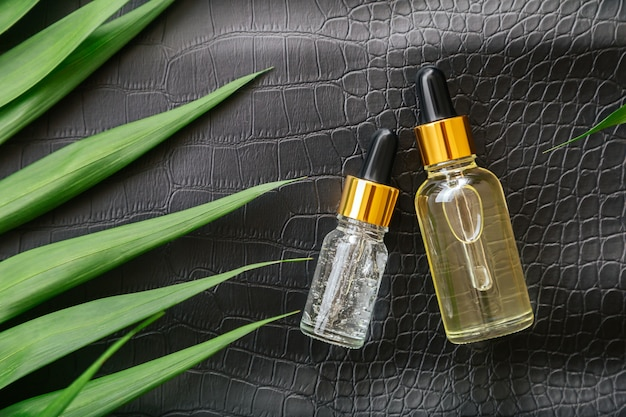 Collagen serum or hyaluronic serum in dropper on black color crocodile skin texture background with palm leaves. skincare cosmetic product bottle. cosmetics health face skin beauty.